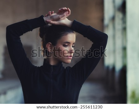 Beautiful girl stretching before workout in abandoned building. - stock photo