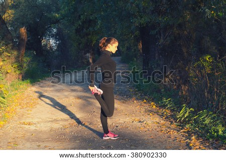 Beautiful girl stretching outdoor before running on sunny spring day. - stock photo