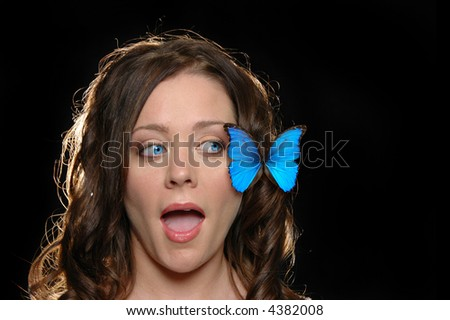 Beautiful girl surprised with butterfly against a black background - stock photo