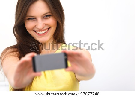Beautiful girl taken taking selfie self-portrait with camera phone - stock photo