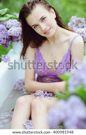 Beautiful girl takes a bath in the garden with lilac flowers, organic skin care