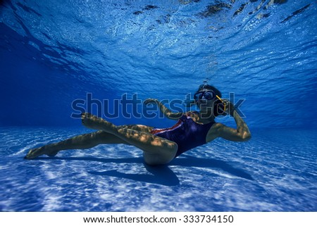 Beautiful girl takes a call to smart phone underwater - stock photo