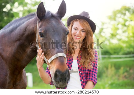 Beautiful girl taking care of her horse. Focus on girl. Warm image tone. Soft focus - stock photo