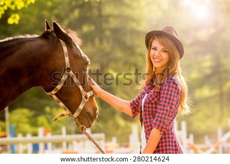 Beautiful girl taking care of her horse. Focus on girl. Warm image tone. Soft focus