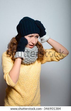 beautiful girl talking on the phone, in a bright yellow color, lifestyle winter clothes studio photo isolated on a gray background - stock photo