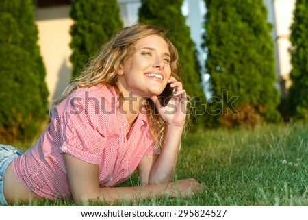 Beautiful girl talking on the phone in yard