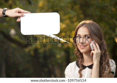 Beautiful girl talking with cell phone in park - stock photo