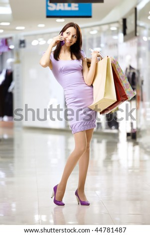 Beautiful girl talks by a mobile phone in shop - stock photo