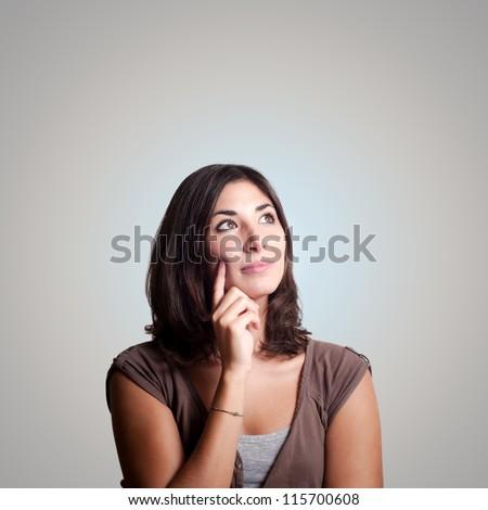 beautiful girl thinking on gray background - stock photo