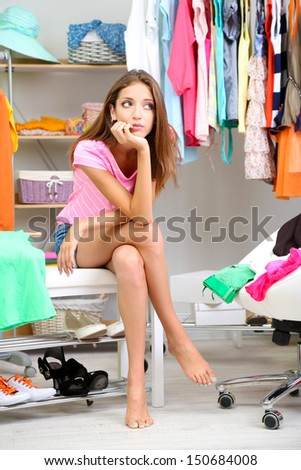 Beautiful girl thinking what to dress in walk-in closet - stock photo