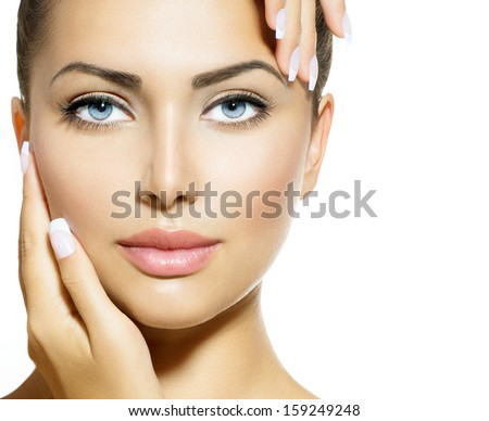 Beautiful Girl Touching her Face. Beauty Spa Woman Portrait. Perfect Fresh Skin. Pure Beauty Model Girl. Youth and Skin Care Concept. Isolated on White Background. Looking at Camera - stock photo