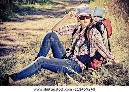Beautiful girl tourist making her journey at the mountains. - stock photo