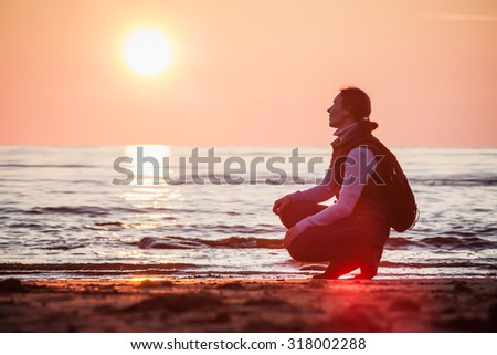 Beautiful girl traveling with a backpack on the beach. - stock photo