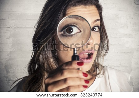Beautiful girl using magnifying glass