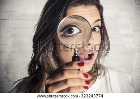 Beautiful girl using magnifying glass - stock photo