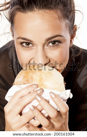 beautiful girl voraciously eating her sandwich - stock photo