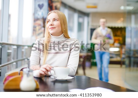 beautiful girl waiting for boyfriend in cafe. romantic date in a cafe. attractive girl sits at a table with a cup of coffee. behind her is a man with flowers. blurry, selective focus - stock photo