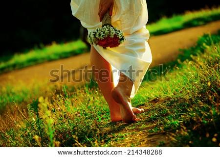 Beautiful girl walking at sunset - stock photo