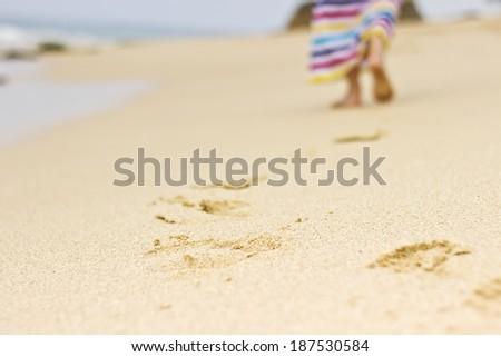 Beautiful girl walking in colorful dress on the beach leaving footprints in the sand. Horizontal image. Sri Lanka, Ceylon - stock photo