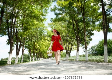 beautiful girl walking in nature and holding  a basket with flowers