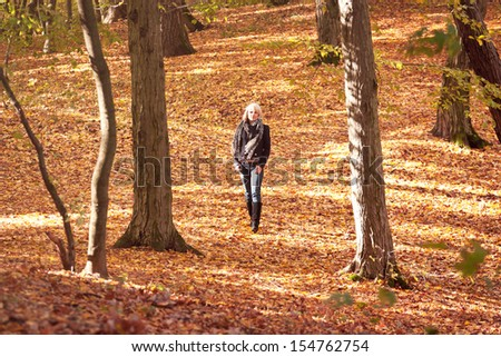 Beautiful girl walking in the autumn park