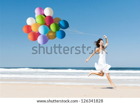 Beautiful girl walking in the beach while holding colored balloons - stock photo