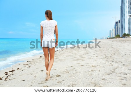 beautiful girl walking on the beach. - stock photo