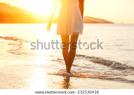 Beautiful girl walking on the beach at sunset, freedom concept  - stock photo
