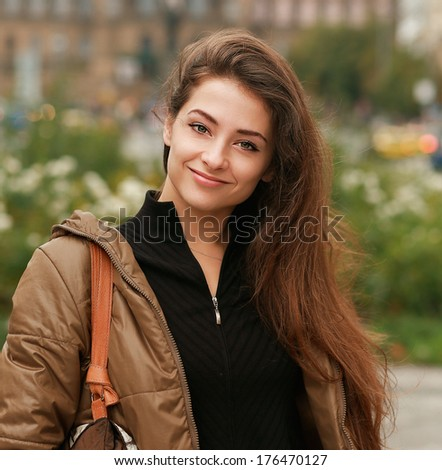 Beautiful girl walking on the city street with smile. Vintage portrait
