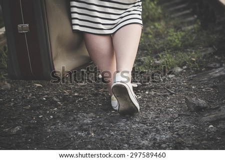 Beautiful girl walking on the railroad