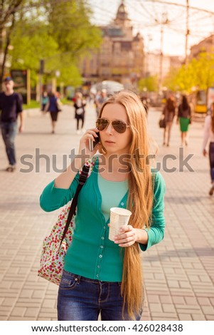 Beautiful girl walking on the street with coffee and talking on phone - stock photo