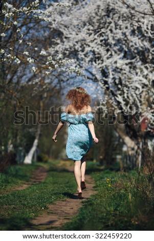 beautiful girl walks in the lush garden dressed in a wreath - stock photo