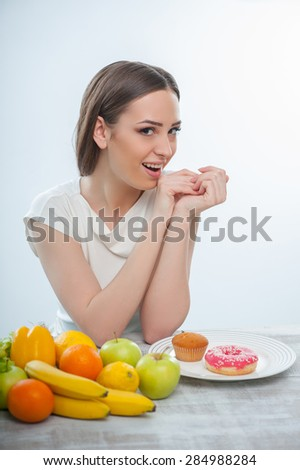 Beautiful girl wants to eat fruits and donuts. She is looking at the camera passionate and smiling. Isolated on a white background - stock photo