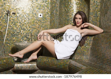 Beautiful girl warped in towel relaxing in spa - stock photo