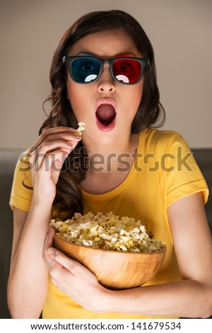 Beautiful girl watching movie with 3d glasses and eating popcorn. She is very expressive - stock photo