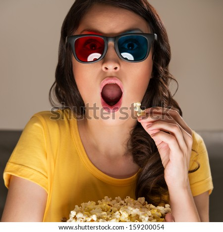 Beautiful girl watching movie with 3d glasses and eating popcorn. She is very expressive