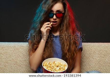 Beautiful girl watching movie with glasses and eating. - stock photo