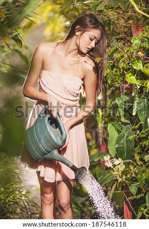 beautiful girl watering flowers in the garden