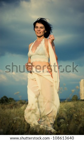 Beautiful girl waving white scarf in a summer field over blue sky - stock photo