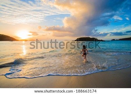 Beautiful girl wearing a bikini walking out of the ocean at sunset in Cinnamon Bay, St. John, USVI