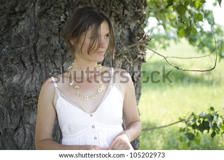 Beautiful girl wearing a daisy chain necklace in the countryside