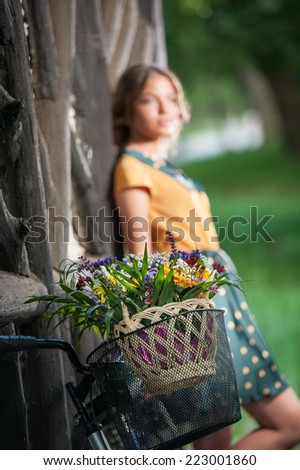 Beautiful girl wearing a nice dress with college look having fun in park with bicycle carrying a beautiful basket. Vintage scenery. Pretty retro blonde girl with bike and basket with flowers - stock photo