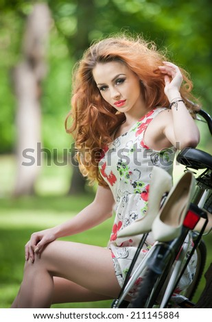 Beautiful girl wearing a nice short dress having fun in park with bicycle. Pretty long hair woman with romantic look resting on her bike in a sunny day. Gorgeous curly female relaxing smiling outdoor. - stock photo