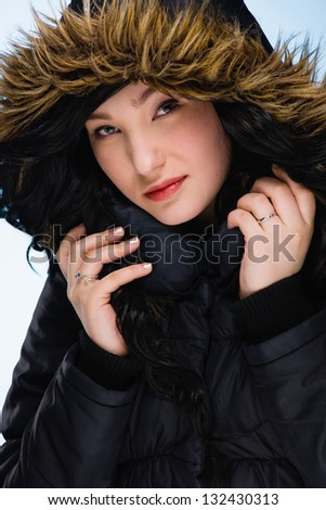 Beautiful girl wearing hood, light blue background, vertical format