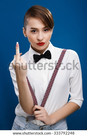 Beautiful girl, wearing in white shirt, brace and black bow, showing rude gesture, on the blue background, in studio, waist up