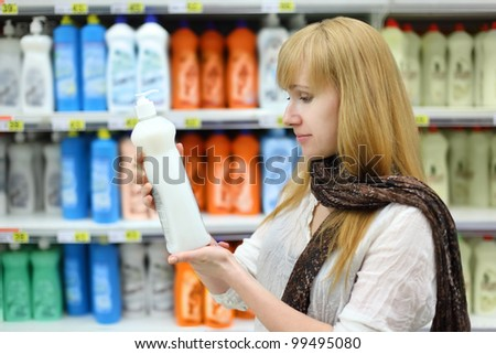 Beautiful girl wearing scarf holds abstergent in shop; shallow depth of field - stock photo
