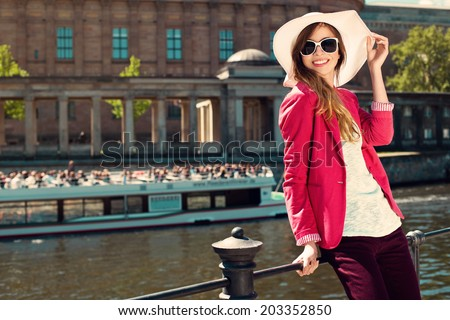 Beautiful girl wearing summer hat and sunglasses at riverside  - stock photo