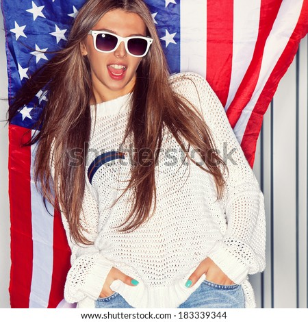 Beautiful girl wearing sunglasses in front of a flag of the United States - stock photo