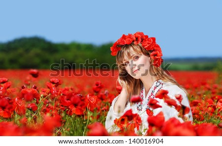 Beautiful girl wearing ukrainian traditional embroidered dress and  poppy headband standing in a poppy field - stock photo