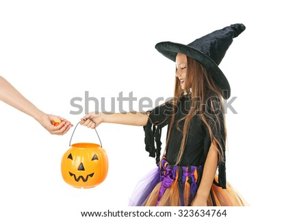Beautiful girl witch and basket for candies on a white background